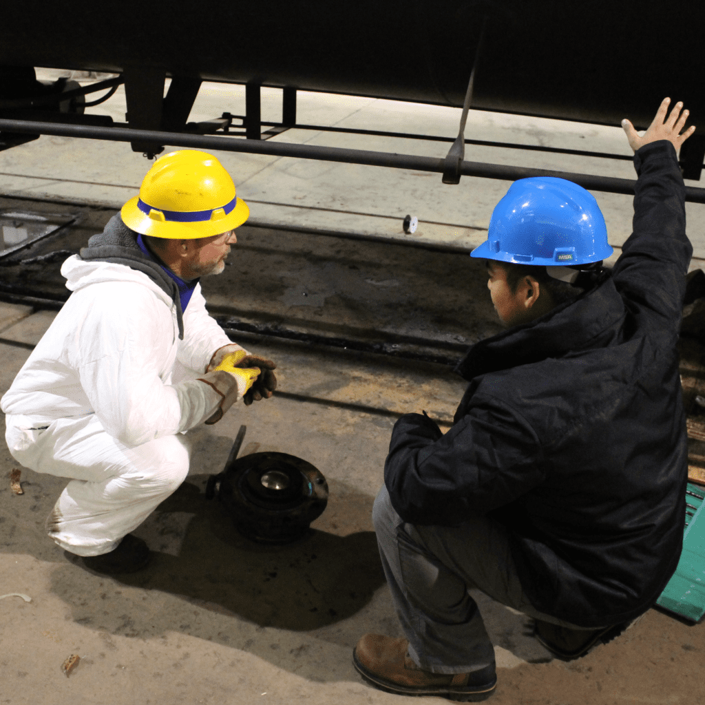 Two guys working on a rail car project